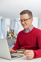 Smiling man using credit card and laptop to shop online at home during Christmas
