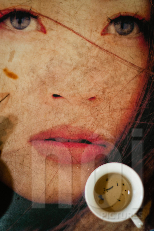 In a Hanoi barber shop, a cup of tea sits on an old table which is decorated with the face of a pin-up girl, Vietnam, Southeast Asia