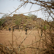 A field commander of Sudan People's Liberation Movement (SPLA-N) walks by in Jebel Kwo military base near Tess village in the rebel-held territory of the Nuba Mountains in South Kordofan. SPLA-North, an historical ally of South Sudan's former rebel forces SPLA, has been fighting the Sudanese Army Forces (SAF) over the right to autonomy and of the end of persecution of Nuba people by the regime of President Bashir.