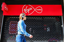 © Licensed to London News Pictures. 07/05/2020. London, UK. A woman walks past a Virgin Media store in north London. Virgin Media and O2 are to merge and create a £31 billion media and telecoms giant. The merger is expected to be completed by 2021. Photo credit: Dinendra Haria/LNP