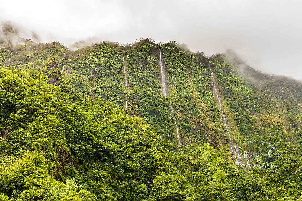 Waterfalls cascading down the vertical cliffs in  Papenoo Valley, Tahiti, French Polynesia