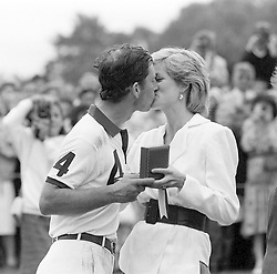 File photo dated 27/07/86 of the Princess of Wales presenting her husband, the Prince of Wales, with a prize and a kiss after he played for the England II team against Chile at the Cartier International Polo Spectacular at the Guards Polo Club in Windsor Great Park, Berkshire.