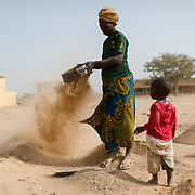 Talato Kabre lives with her husband, Sidpayete Rouamba, and two of their four children in Wapassi, an informal settlement in Burkina Faso's capital, Ouagadougou. Her only income derives from sweeping up sand in a nearby open space with a hand broom, sieving it, and attempting to sell it for construction. A small pile costs CFA 1000 ($1.65); she says she sometimes goes weeks withou selling anything. Sidpayete is a labourer but and is frequently out of work. Talato is accompanied by her youngest child, Julien Rouamba (3).