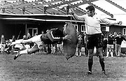 Colin Meads assisting at a rugby coaching school facilitated by NZRU reps Ivan Vodanovich and Bill Freeman, held at Taumarunui on 30 May 1976.<br />