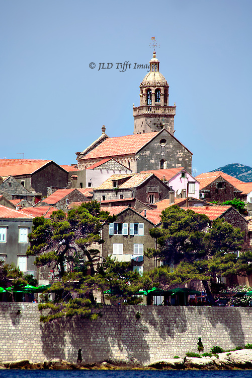 Korcula: A few houses with a small church above and the town wall below.  Telephoto view from the sea as the sailboat departs.