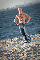 Fitness model & bodybuilder on beach with ripped abs and shirt off.