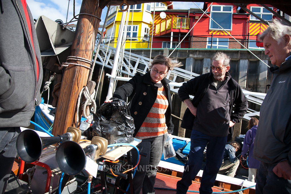 Lise Autogena shows the captain of the ship Sovereign how to work the installed fog horn controle box.  Preparations of the Fog Horn Requiem a few hours before the concert is about to start. Last minute installations and adjustments in the workshop and on the ships participating with remote controled horns. <br /> <br /> A REQUIEM FOR THE FOGHORN, PERFORMED BY SEVENTY FIVE BRASS PLAYERS, A FOGHORN AND AN ARMADA OF SHIPS PLAYING THEIR COSTUMISED AND REMOTE CONTROLED FOG HORNS.<br /> <br /> A project by Danish artist, Lise Autogena, in collaboration with Joshua Portway and composer Orlando Gough. The performance took place by Souter Light House by South Shields, UK with thousands of spectators and more than 50 ships off-shore.