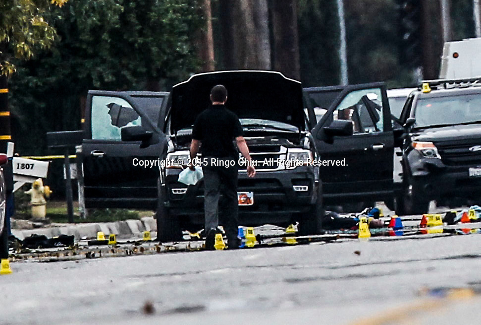 FBI, San Bernardino City and San Bernardino County Sheriff's officials continue documenting and investigating the scene where a Black SUV that was involved in a police shootout with suspects, Friday, Dec. 4, 2015, in San Bernardino, California. The FBI said Friday it is officially investigating the mass shooting in California as an act of terrorism, while a U.S. law enforcement official said the woman who carried out the attack with her husband had pledged allegiance to the Islamic State group and its leader on Facebook.
