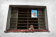 An elderly woman looks out the window of her home while waiting for Pope John Paul II' s motorcade to go by in  Havana, Cuba. (1998)