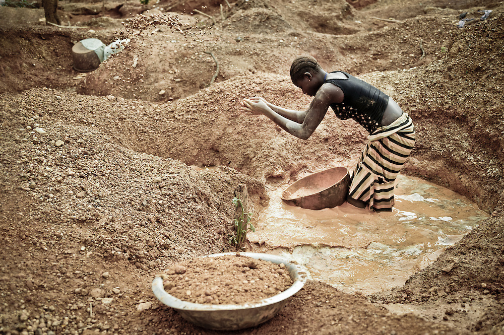 Stock photograph of an African woman panning for gold in Guinea in an old miner's hole using nothing more than a calabash and an understanding of fluid dynamics.