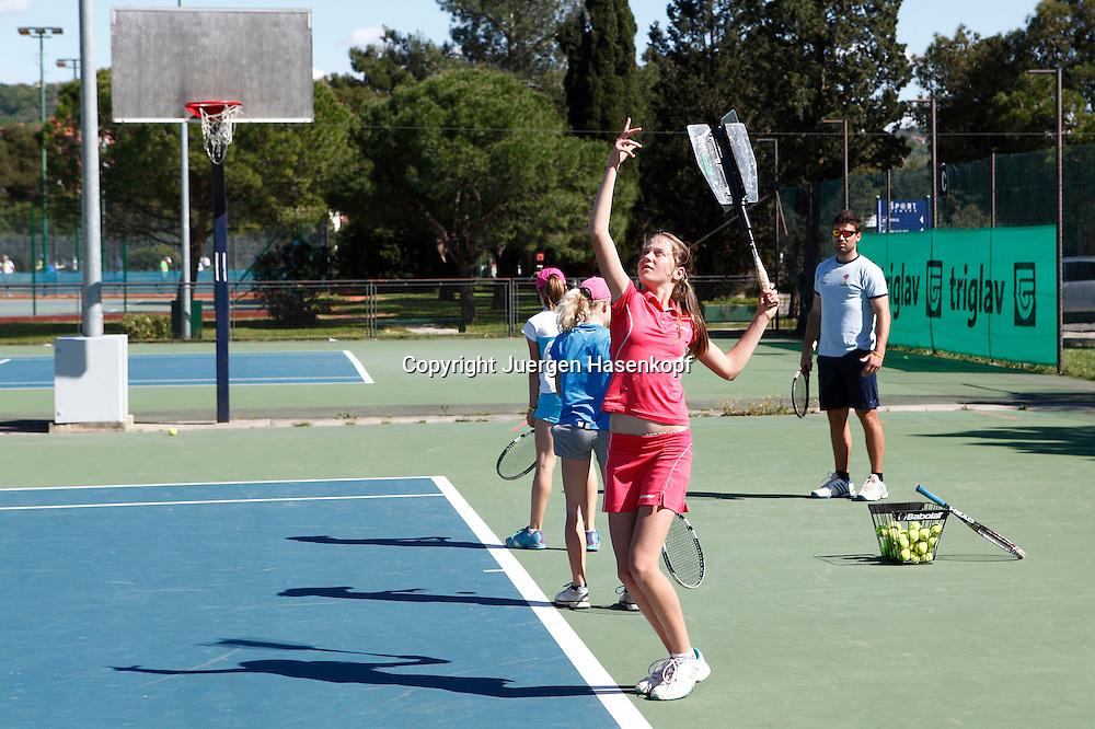 Tennis Training Camp fuer Kinder in Portoroz, Slowenien,<br /> Trainer beobachtet drei Maedchen wie sie den Service,Aufschlag ueben,Uebung,Ganzkoerper,Querformat,