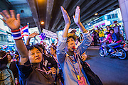 """20 DECEMBER 2013 - BANGKOK, THAILAND:  Anti-government protestors on Silom Rd, the """"Wall Street"""" of Bangkok. Thousands of anti-government protestors, supporters of the so called Peoples Democratic Reform Committee (PRDC), jammed the Silom area, the """"Wall Street"""" of Bangkok, Friday as a part of the ongoing protests against the caretaker government of Yingluck Shinawatra. Yingluck dissolved the Thai Parliament earlier this month and called for national elections on Feb. 2, 2014. The protestors want the elections postponed and the caretaker government to step down. The Thai election commission ruled Friday that the election would go on dispite the protests.         PHOTO BY JACK KURTZ"""