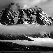 The Teton Range peaking out of morning fog in Jackson Hole valley in Grand Teton National Park, Wyoming.
