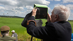 © Licensed to London News Pictures. 05/06/2014. A D Day veteran uses his IPAD to photograph a parachute jump over the fields of Ranville in Normandy during the 70th Anniversary of the D Day landings in Normandy.  Photo credit : Alison Baskerville/LNP