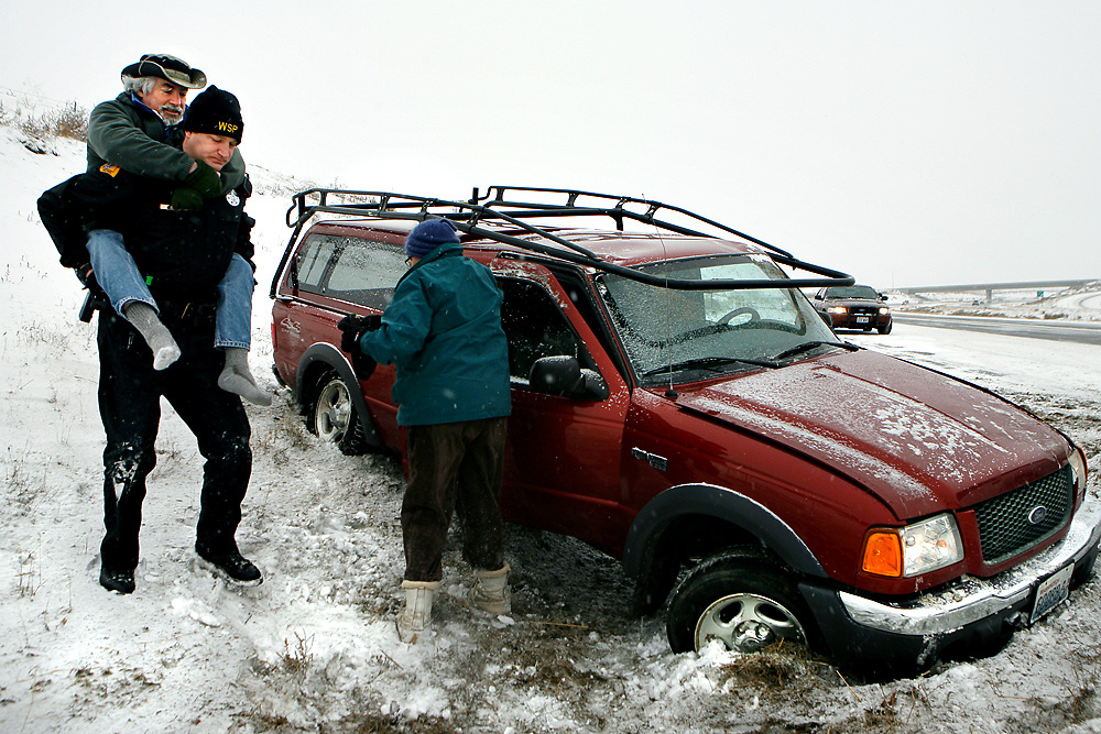 Washington State Patrol Sgt. Zach Elmore helps Pete Rieke of Pasco out of his truck after Rieke went off the road on westbound Highway 182 while wife Jenny Rieke retrieves items from his truck.