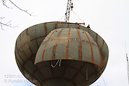 Crane mounted atop half-built water tower lifts huge steel plate into place; Kirkwood, Missouri.