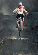 DETROIT, MICHIGAN - USA -  A woman downhill mountain bike rider hits a jump. (Photo by Bryan Mitchell)