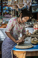 Woman in the village of Mingun near Mandalay traditionally prepares Thanaka, a yellow paste worn to beautify and protect skin from the sun.