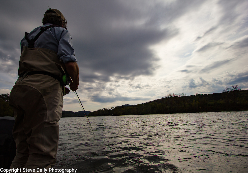 Man fly fishing in waders on a boat under grey skies