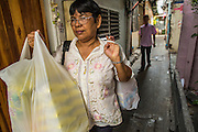 """11 JANUARY 2013 - BANGKOK, THAILAND:    A woman walks home with her shopping in the Ban Krua neighborhood in Bangkok. The Ban Krua neighborhood of Bangkok is the oldest Muslim community in Bangkok. Ban Krua was originally settled by Cham Muslims from Cambodia and Vietnam who fought on the side of the Thai King Rama I. They were given a royal grant of land east of what was then the Thai capitol at the end of the 18th century in return for their military service. The Cham Muslims were originally weavers and what is known as """"Thai Silk"""" was developed by the people in Ban Krua. Several families in the neighborhood still weave in their homes.                PHOTO BY JACK KURTZ"""