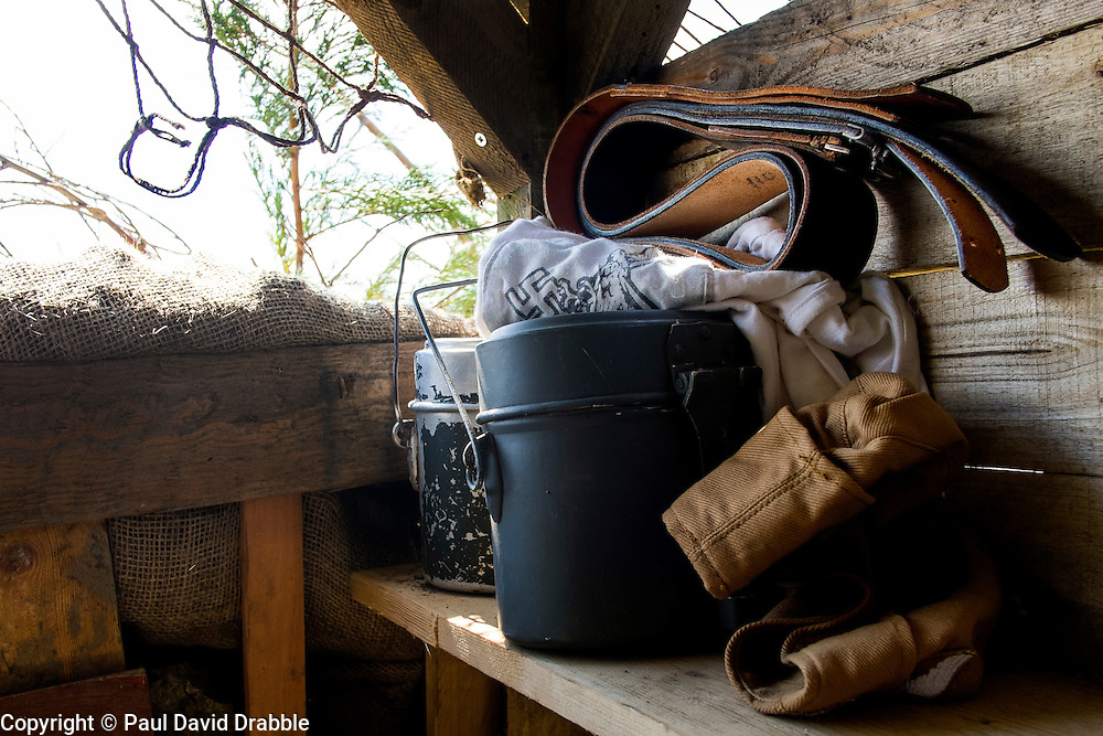 German Luftwaffe/Fallschirmj&auml;ger Mess tins gloves and belt sit on a shelf in camouflaged bunker at the Yorkshire War weekend<br />