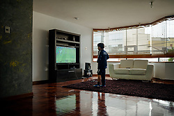 NO WEB/NO APPS - (Text available) A young boy plays on a playstation in his house in Las Casuarinas urbanization, in Lima, Peru in May 2017. In Peru's capital Lima, a three-meter-high concrete wall topped with reels of razor wire separates two areas. The so-called 'Wall of Shame' - sometimes nicknamed 'Peru's Berlin Wall' - divides the urbanisation of Las Casuarinas, where some of the country's richest inhabitants live, and the poor suburb of Vista Hermosa next door. It was initially put up over fears that the inhabitants from the poor neighbourhood would steal from wealthy fellow citizens living nearby. On the rich side of the wall, the price for a square meter can exceed 2,000 dollars. To enter the area, you must show your ID to the guards watching the gate at the bottom of the hill. Former high-ranking politicians and bank directors live here. Their houses are surrounded by lush gardens and swimming pools despite the scarcity of water. Meanwhile, on the San Juan de Miraflores side, residents often fall victim to robbery and theft. They live in houses of barely 25m², made from scrap material, surrounded by the sand and earth characteristic of Lima's desert landscape. Photo by Giacomo D'Orlando/ABACAPRESS.COM