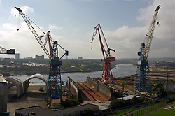 Swan Hunter shipyard cranes on left; now closed,  Other riverside derelict shipyards beyone towards Walker, Wallsend; Tyneside UK 2006