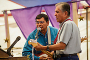 "12 JULY 2012 - FT DEFIANCE, AZ: Musicians perform worship music at the 23rd annual Navajo Nation Camp Meeting in Ft. Defiance, north of Window Rock, AZ, on the Navajo reservation. Preachers from across the Navajo Nation, and the western US, come to Navajo Nation Camp Meeting to preach an evangelical form of Christianity. Evangelical Christians make up a growing part of the reservation - there are now more than a hundred camp meetings and tent revivals on the reservation every year. The camp meeting in Ft. Defiance draws nearly 200 people each night of its six day run. Many of the attendees convert to evangelical Christianity from traditional Navajo beliefs, Catholicism or Mormonism. ""Camp meetings"" are a form of Protestant Christian religious services originating in Britain and once common in rural parts of the United States. People would travel a great distance to a particular site to camp out, listen to itinerant preachers, and pray. This suited the rural life, before cars and highways were common, because rural areas often lacked traditional churches.PHOTO BY JACK KURTZ"