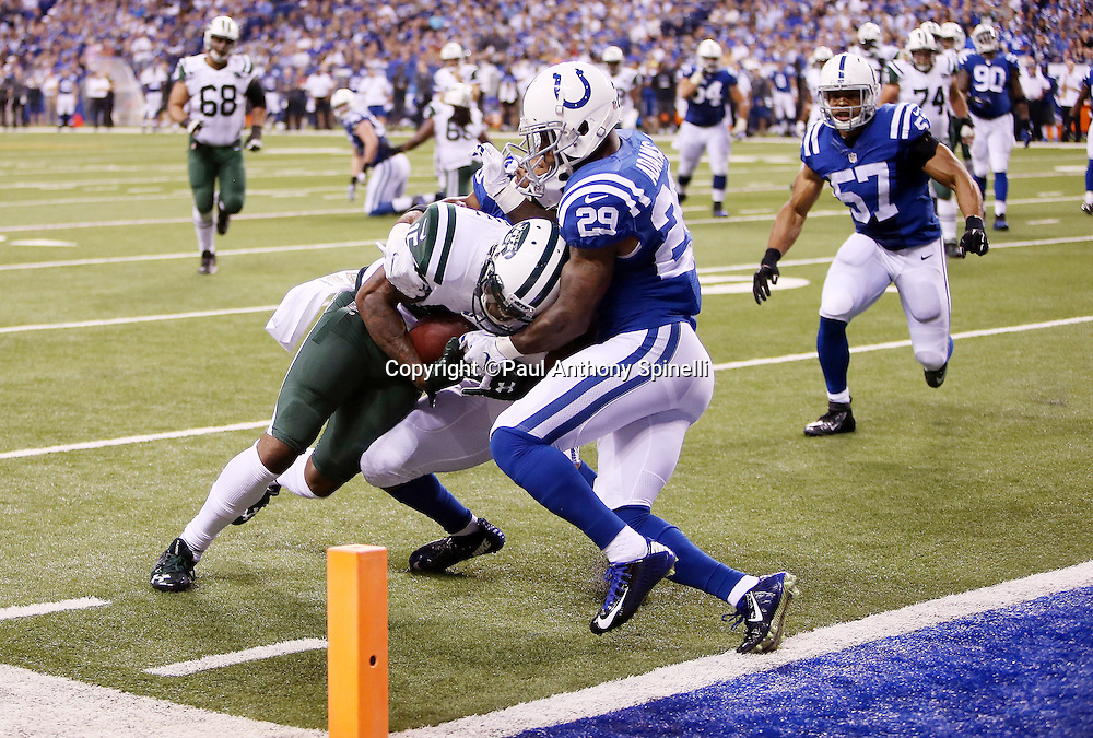 New York Jets wide receiver Brandon Marshall (15) gets gang tackled by Indianapolis Colts defensive back Jalil Brown (25) and Indianapolis Colts strong safety Mike Adams (29) as he pushes toward the pylon and a fourth quarter touchdown reception of 15 yards that gives the Jets a 17-7 Jets lead during the 2015 NFL week 2 regular season football game against the Indianapolis Colts on Monday, Sept. 21, 2015 in Indianapolis. The Jets won the game 20-7. (©Paul Anthony Spinelli)