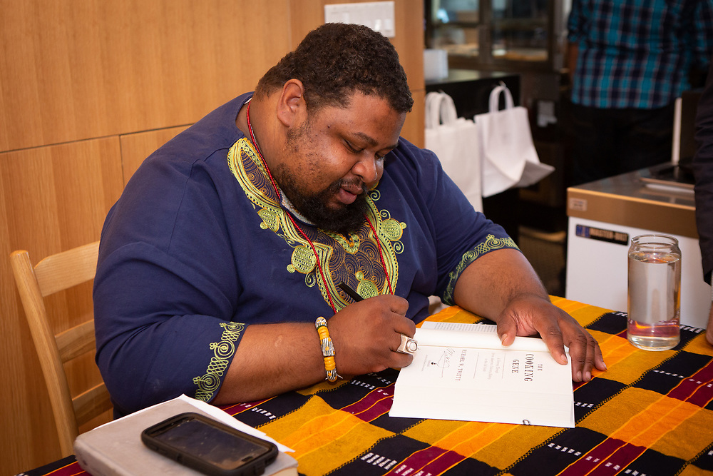 Brooklyn, NY - May 9, 2018:  Chef and author Michael Twitty leads the Guest Chef Series at the Brownsville Community Culinary Center, signing and reading from his book, while the BCCC team prepares and presents a meal designed to recall African and African-American food history.<br /> <br /> CREDIT: Clay Williams.<br /> <br /> &copy; Clay Williams / http://claywilliamsphoto.com