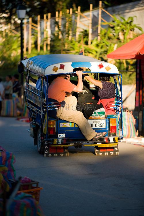 Laos - Luang Prabang, Tuk Tuk overloaded with heavy passengers.
