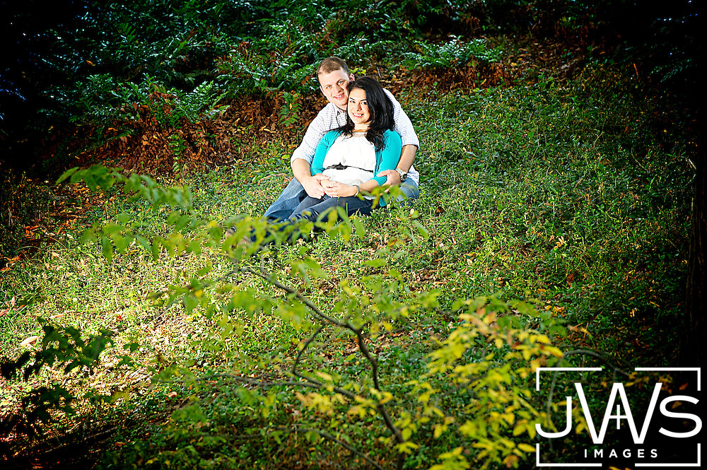 A couple sitting on a hill covered in green grass embracing each other