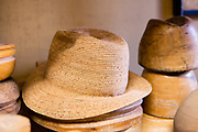 A straw hat rests on a stack of wooden hat blocks.