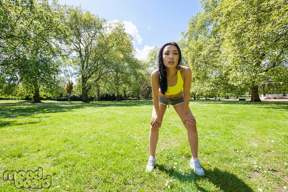 Full length of tired fit woman taking a break while exercising in park