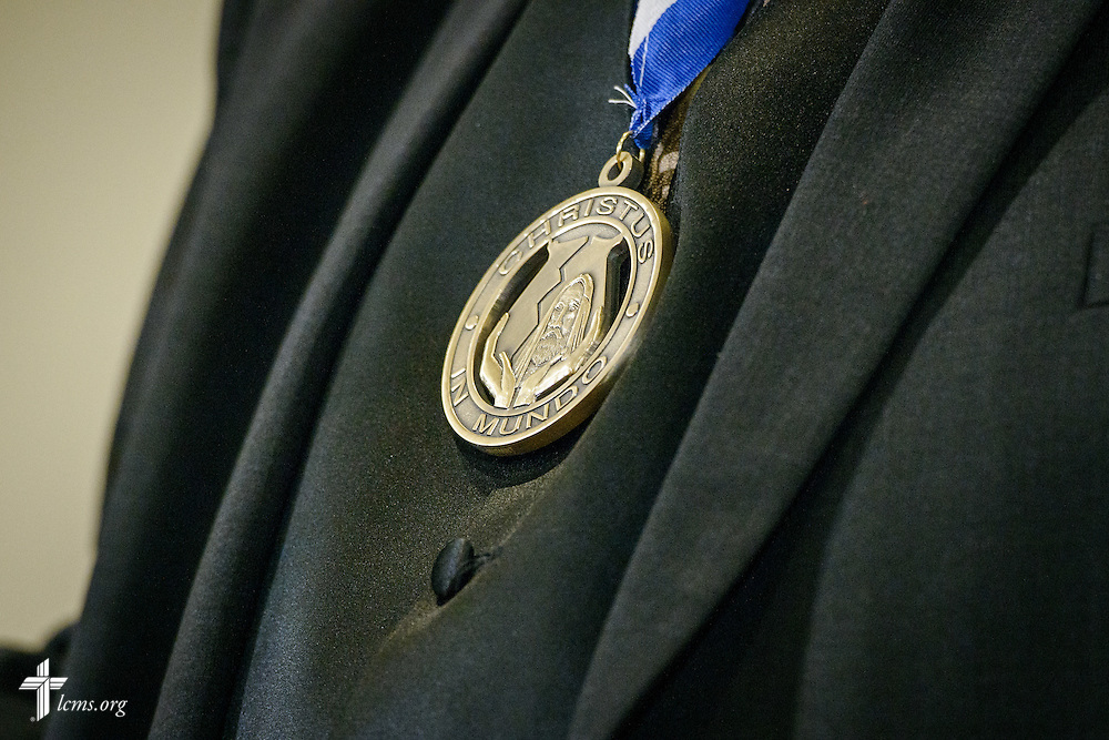 "A detail photograph of a ""Christus in Mundo (""Christ in the World"") award, worn by the Rev. Dr. William Wagner, as he speaks at the SPM Zion XVI Conference award banquet on Saturday, Sept. 17, 2016, at the National Shrine of Our Lady of the Snows in Belleville, Ill. LCMS Communications/Erik M. Lunsford"