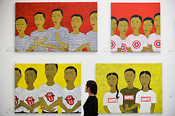 © Licensed to London News Pictures. 12/09/2018. LONDON, UK. A staff member views works Min Zaw (Myanmar) at the preview of START, a contemporary art fair comprising eclectic works from a variety of international emerging artists.  The fair takes place at the Saatchi Gallery in Chelsea 13 to 16 September 2018.  Photo credit: Stephen Chung/LNP