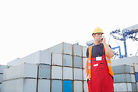 Male worker using walkie-talkie in shipping yard