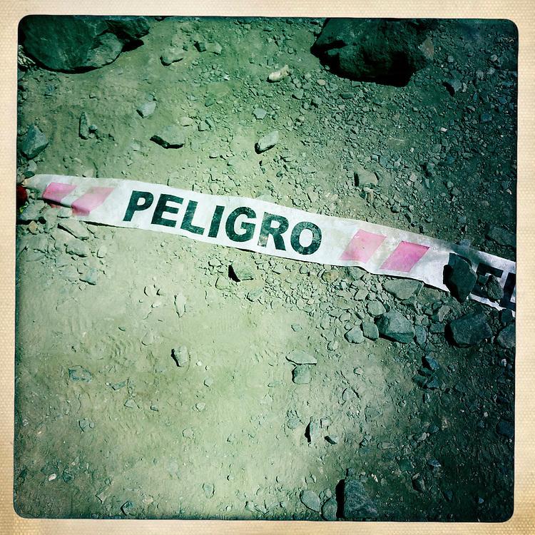 """Una senal de advertencia es vista en el suelo del campamento Esperanza. Plan B, es un ensayo fotografico basado en aquellas cosas que la mirada somera no permite ver, de los días de espera, angustia, soledad y fe que las familias de los 33 hombres atrapados en la mina San Jose dejaron en el paisaje arido del desierto de Atacama tras el esperado rescate. """"Plan B"""", tambien es un acto de fe personal, por intentar plasmar en un relato diferente, sin más pretensión que la mirada interna a los sentimientos que esa montaña atrapó implacable y para siempre, pero que bajo la mirada superficial de los medios no permite escudriñar por tratarse de pequeños fragmentos que apelan a emociones individuales y no a la masividad que persiguen los reportes de prensa. Este ensayo es una invitación abierta a descubrir los pequeños milagros que florecieron en la montaña y en el día a día de cada una de las familias que nunca dejaron de creer en la vida, aun así se enfrentaran a la inmensidad del desierto y a las minimas espectativas de vida que el lugar entregaba.""""Plan B"""", esta constituido por fotografías ejecutadas en su totalidad con un telefono iPhone 4 y la aplicacion Hipstamatic. ROBERTO CANDIA / REVISTA NUESTRA MIRADA"""