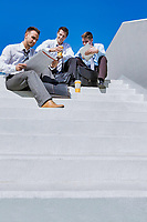 Group of handsome business colleagues sitting on stairs
