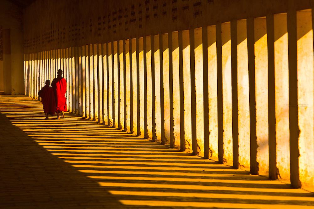 Monks walking down hallway in the Shwezigon Pagoda, Bagan, Myanmar (Burma)