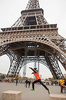 A young boy jumps from one concrete chair to another at the base of the Eiffel Tower in Paris, France.