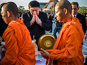 20 JANUARY 2017 - BANGKOK, THAILAND: Pol Gen ASWIN KWANMUANG, the Governor of Bangkok, prays as Buddhist monks walk past him during a merit making ceremony on the plaza in front of Bangkok's City Hall. Hundreds of municipal workers and civil servants made merit by praying and presenting alms to 89 Buddhist monks Friday to mark 100 days of mourning since the death of revered Bhumibol Adulyadej, the Late King of Thailand. The significance of 89 monks is that the King, who died on October 13, 2016, was a few weeks short of his 89th birthday.        PHOTO BY JACK KURTZ