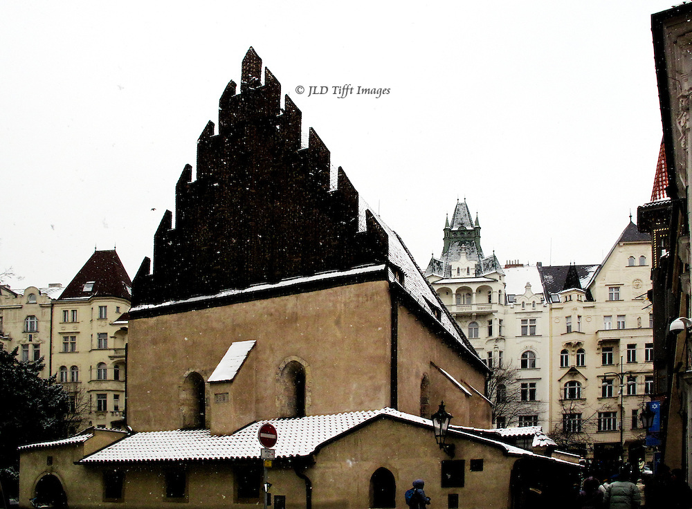 """Prague, old synagogue, exterior in snow, surrounded by 18th century apartment buildings erected after the old Jewish quarter was cleared.  The attic behind the high gabled roof is said to contain the """"golem"""" but is no longer accessible."""