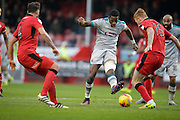 Omar Bogle takes shot at goal with Josh Yorwerth defending during the EFL Sky Bet League 2 match between Crawley Town and Grimsby Town FC at the Checkatrade.com Stadium, Crawley, England on 26 November 2016. Photo by Jarrod Moore.