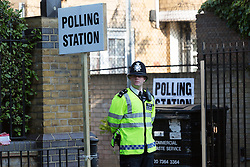 © Licensed to London News Pictures. 11/06/2015. London, UK. A police officer outside a polling station in Wapping, Tower Hamlets, east London. Tower Hamlets residents go to the polls today to vote for a new Mayor of Tower Hamlets after Lutfur Rahman was removed from office for fraud in corrupt practices by an election court earlier this year. Photo credit : Vickie Flores/LNP