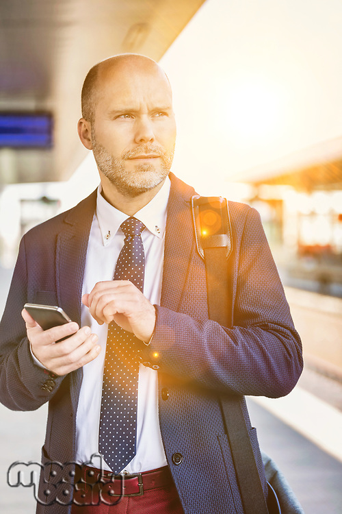 Portrait of businessman using smartphone while waiting for the train in station