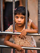 "22 OCTOBER 2015 - YANGON, MYANMAR: A Hindu girl stands in the doorway of Sri Kali temple in Yangon on the last day of Navratri. Navratri, literally ""nine nights"" is a Hindu festival devoted to the Goddess Durga. Navratri festival combines ritualistic puja (prayer) and fasting. Navratri in India follows the lunar calendar and is celebrated in September/October as Sharad Navratri. It's widely celebrated in countries in Southeast Asia that have large Hindu communities, including Myanmar (Burma). Many of Myanmar's Hindus are descendants of Indian civil servants and laborers who came to Myanmar when it was the British colony of Burma.   PHOTO BY JACK KURTZ"