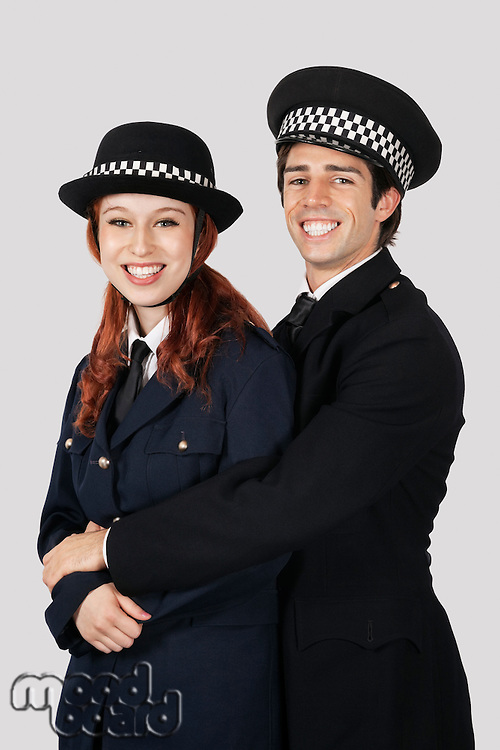 Portrait of young police officers embracing against gray background