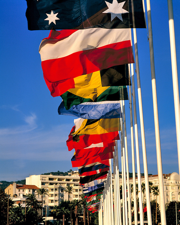 Colorful flags line the Boulevard de la Croisette on the Mediterranean Sea at Cannes on the French Riviera.