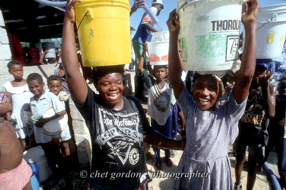 Young Haitian girls balance 5-gallon water buckets on their heads at a water pumping station in the Cite Soliel neighborhood of Port-au-Prince, Haiti. October 1993.